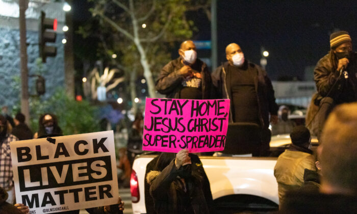 Protesters hold up signs protesting a Christian homeless outreach event while blocking traffic at Skid Row in Los Angeles on Dec. 30, 2020. (John Fredricks/The Epoch Times)