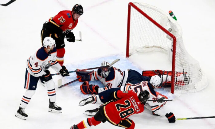Elias Lindholm of the Calgary Flames scores a goal on Mike Smith of the Edmonton Oilers during the second period in an exhibition game on July 28, 2020. (Jeff Vinnick/Getty Images)