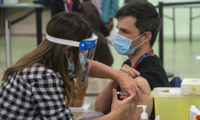A nurse injects a man with a COVID-19 vaccine in Edmonton on Dec. 15, 2020. (The Canadian Press/Jason Franson)