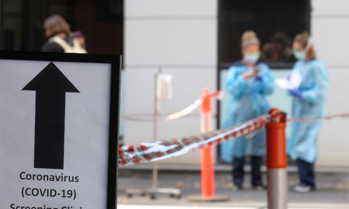 A sign directing people to the COVID-19 screening area is posted outside the Royal Melbourne Hospital in Melbourne, Australia on March 11, 2020. (Luis Ascui/Getty Images)