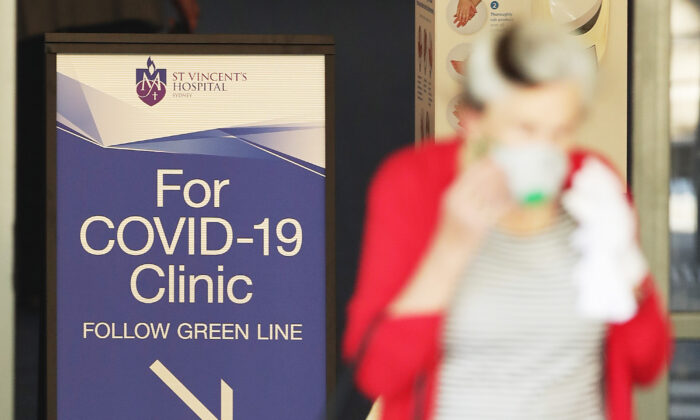 People pass signs for a COVID -19 Clinic as they enter or exit St Vincent's hospital in Sydney, Australia on March 18, 2020. (Mark Metcalfe/Getty Images)