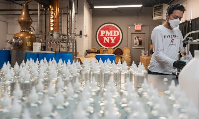 An employee fills a bottle with hand sanitizer at Port Morris Distiller in New York City on April 21, 2020. (David Dee Delgado/Getty Images)