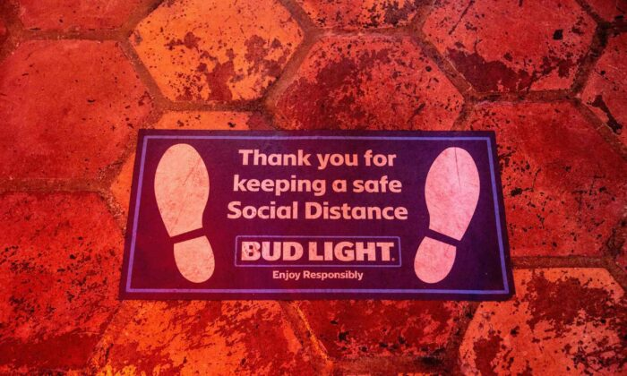 A sign encouraging social distancing is seen on the floor inside a bar in Austin, Tx., on June 26, 2020. (Sergio Flores/AFP via Getty Images)