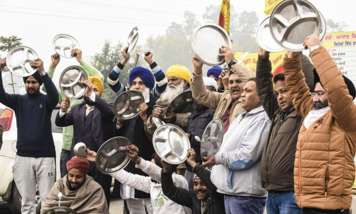 Farmers beat utensils during a protest against the central government's recent agricultural reforms as India's Prime Minister Narendra Modi addressed the nation on the monthly radio programme 'Mann Ki Baat', at the Toll Plaza, on the outskirts of Amritsar on Dec. 27, 2020. (Narinder Nanu/AFP via Getty Images)