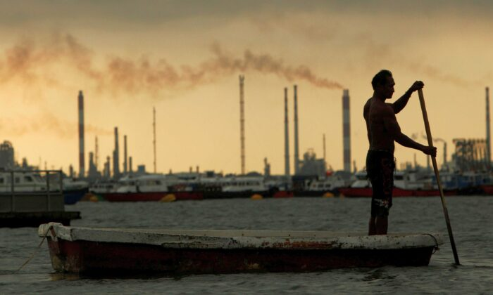 A fisherman rows his dinghy past oil refineries near port terminals in Singapore on Nov. 5, 2013. (Edgar Su/Reuters)