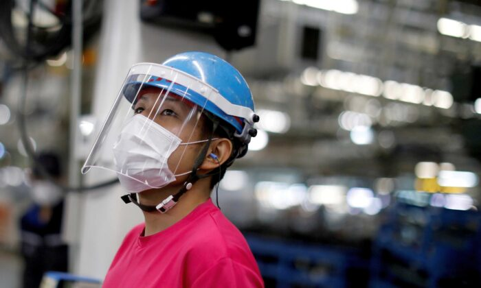 An employee wearing a protective face mask and face guard works on the automobile assembly line as the maker ramps up car production with new security and health measures as a step to resume full operations at Kawasaki factory of Mitsubishi Fuso Truck and Bus Corp., owned by Germany-based Daimler AG, in Kawasaki, south of Tokyo, Japan, on May 18, 2020. (Issei Kato/Reuters)