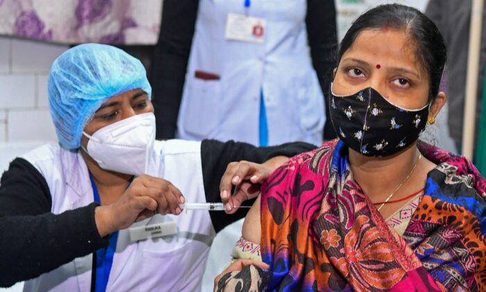 A health official and a volunteer (R) take part in dry run or a mock drill for COVID-19 vaccine delivery at a health center in New Delhi on Jan. 2, 2021. (Prakash Singh via Getty Images)