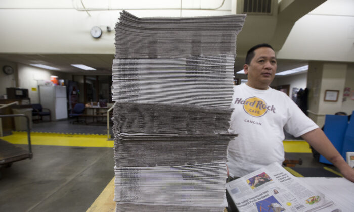 An employee bundles stacks of freshly printed newspapers at the Columbian newspaper in Vancouver, Wash., on April 18, 2018. (Natalie Behring/Getty Images)