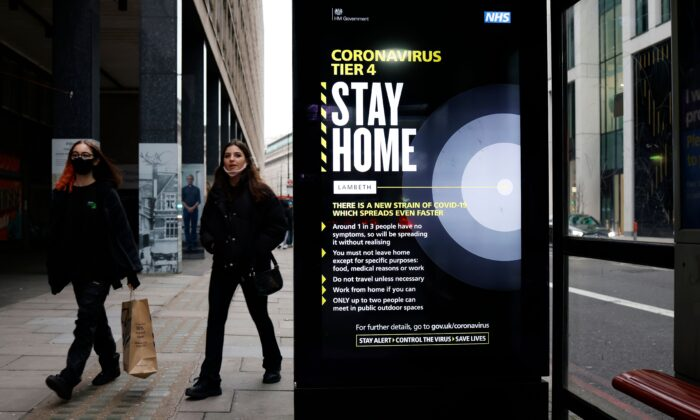 People, some wearing masks, walk past a bus stop with a government message about the CCP virus tier 4 restrictions urging people to stay home in London on Dec. 29, 2020. (Tolga Akmen/AFP via Getty Images)