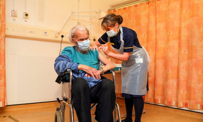 Trevor Cowlett, 88, receives the Oxford University/AstraZeneca COVID-19 vaccine from nurse Sam Foster at the Churchill Hospital in Oxford, England on Jan. 4, 2021. (Steve Parsons/Pool via Reuters)