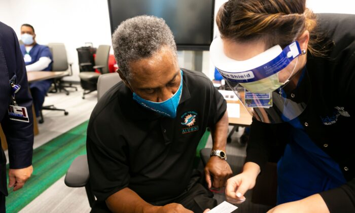 Nat Moore, 69, formerly of the Miami Dolphins, receives his vaccination card after getting his first dose of the Pfizer-BioNtech COVID-19 vaccine at the Christine E. Lynn Rehabilitation Center, in Miami, Fla., on Dec. 30, 2020. (Eva Marie Uzcategui/AFP via Getty Images)