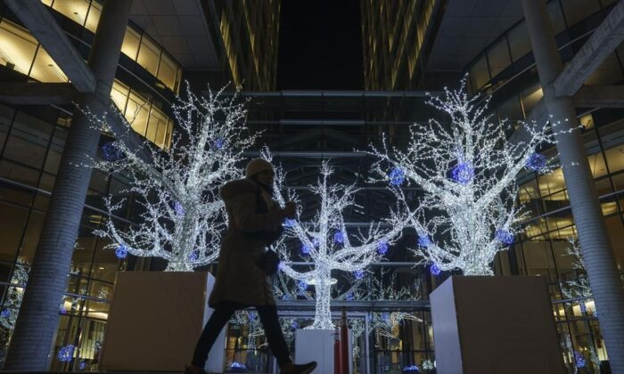 A pedestrian walks by Christmas decorations during the holidays in Montreal on Dec. 18, 2020. (Mario Beauregard/The Canadian Press)