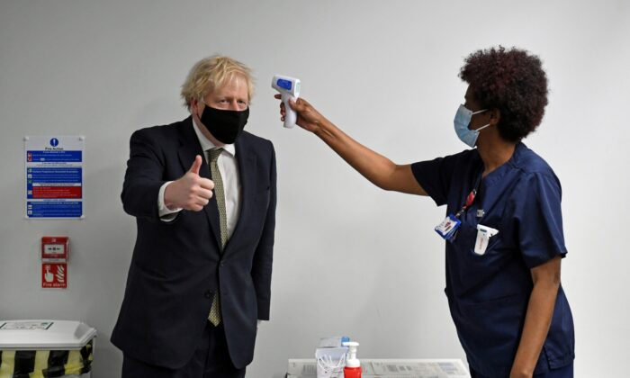 Prime Minister Boris Johnson gives a thumbs up as he has his temperature checked during a visit to Chase Farm Hospital in north London on Jan. 4, 2021. (Stefan Rousseau/Pool/AFP via Getty Images)