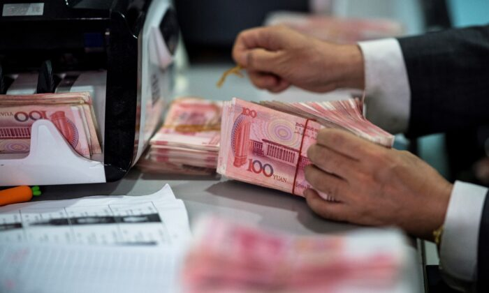 A bank employee counts out 100 yuan notes at a bank in Shanghai on Aug. 8, 2018. (Johannes Eisele/AFP via Getty Images)