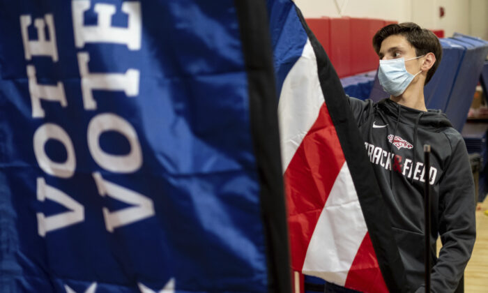 Thomas Hedrich sets up voting flags at a polling location in advance of the Senate runoff elections in Gwinnett County, Ga., on Jan. 4, 2021. (Ben Gray/AP Photo)