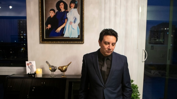 Alireza Ghandchi is photographed in front of a portrait of his wife Faezeh, daughter Dorsa and son Daniel in Richmond Hill, Ont., on Jan. 1, 2021. Ghandchi lost his family after Iranian forces shot down a Ukrainian passenger jet on Jan. 8, 2020. (The Canadian Press/Chris Young)