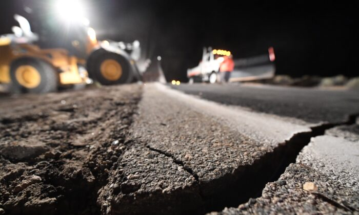 Highway workers repair a hole that opened in the road as a result of the July 5, 2019 earthquake, in Ridgecrest, California, about 150 miles (241km) north of Los Angeles, early in the morning on July 6, 2019. (Robyn Beck/AFP via Getty Images)
