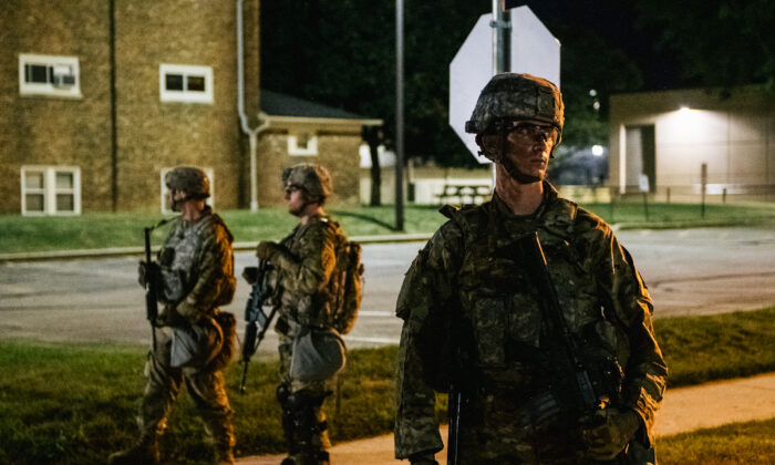 National Guard troops stand guard inside of a fenced area that surrounds several government buildings in Kenosha, Wis., on Aug. 27, 2020. (Brandon Bell/Getty Images)