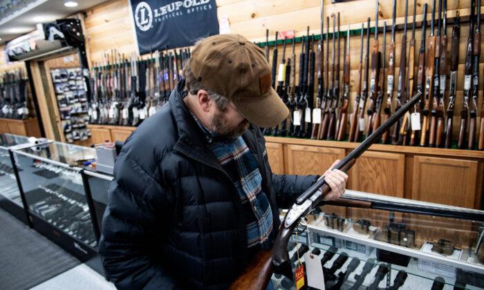 A customer looks at an antique shotgun at a gun shop in Ottawa, Ohio, on Jan. 23, 2020. (Brendan Smialowski/AFP via Getty Images)