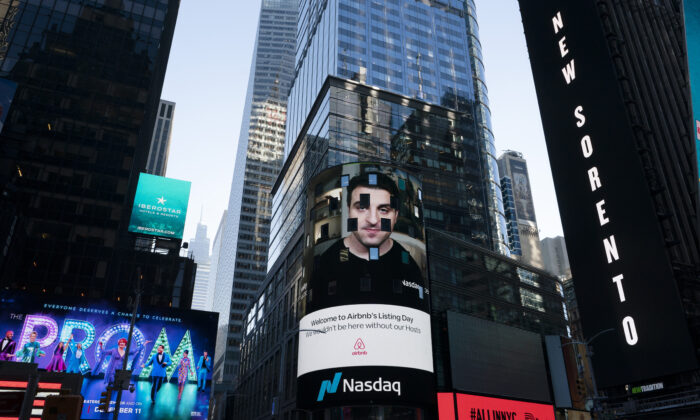 Brian Chesky, CEO of Airbnb, is shown on a screen at the Nasdaq MarketSite in New York on Dec. 10, 2020, the day of Airbnb's initial public offering. (AP Photo/Mark Lennihan)