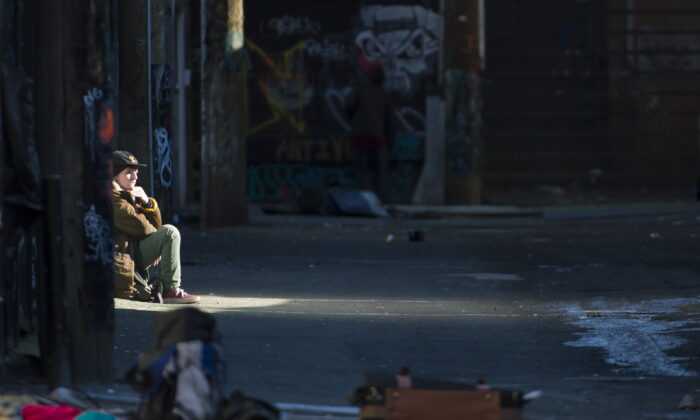 A man sits in an alleyway in Vancouver's Downtown Eastside, Canada, on Feb. 6, 2019. (Jonathan Hayward/The Canadian Press)