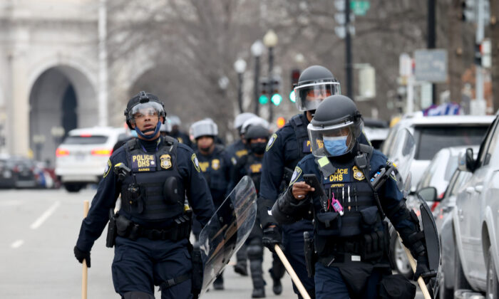 Police officers in riot gear walks towards the U.S. Capitol as a group protesters breached the Capitol building in Washington on Jan. 6, 2021. (Tasos Katopodis/Getty Images)
