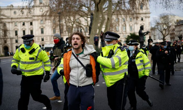 Police officers arrest a protester during an anti-CCP virus lockdown demonstration outside the Houses of Parliament in Westminster, central London, on Jan. 6, 2021. (Tolga Akmen/AFP via Getty Images)
