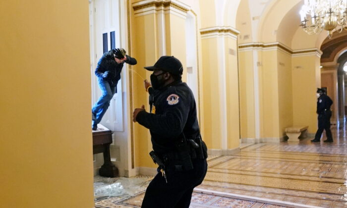 A U.S. Capitol Police officer shoots pepper spray at a protester attempting to enter the Capitol building during a joint session of Congress in Washington on Jan. 6, 2021. (Kevin Dietsch/Pool via Reuters)
