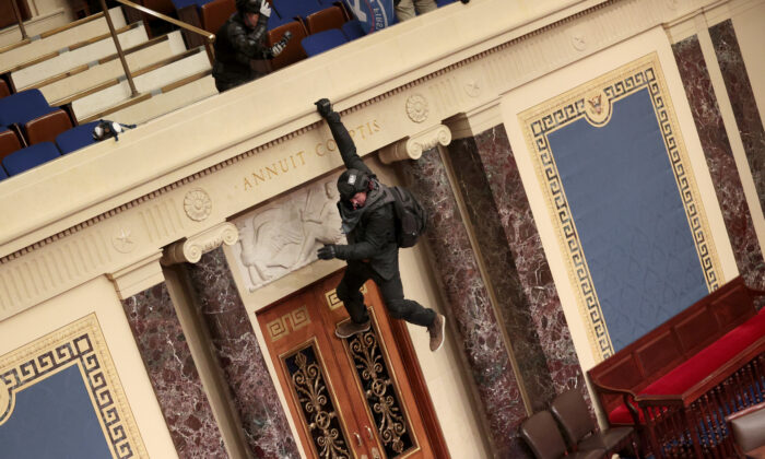A protester is seen hanging from the balcony in the Senate Chamber in Washington on Jan. 6, 2021. (Win McNamee/Getty Images)