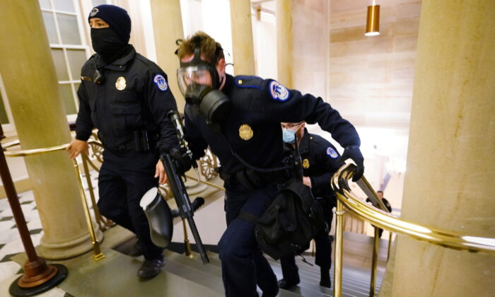 U.S. Capitol Police officers take positions as rioters enter the Capitol building during a joint session of Congress in Washington on Jan. 6, 2021. (Kevin Dietsch/Pool via Reuters)