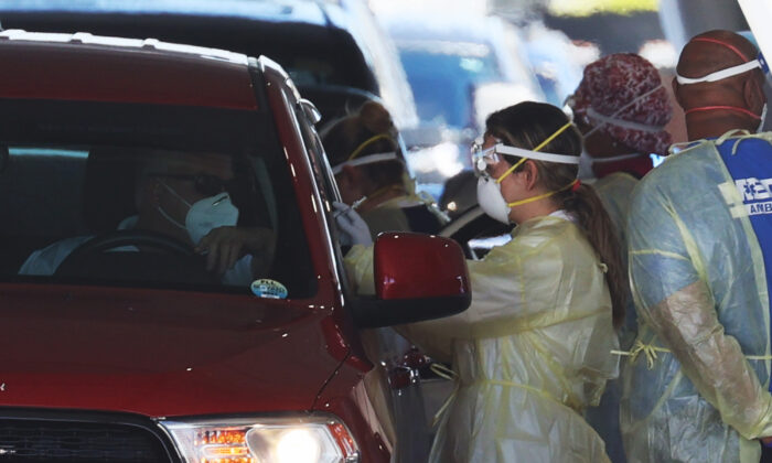 Health care workers administer a COVID-19 vaccination to people at a drive thru site at the Hard Rock Stadium in Miami Gardens, Fla., on Jan. 6, 2021. (Joe Raedle/Getty Images)
