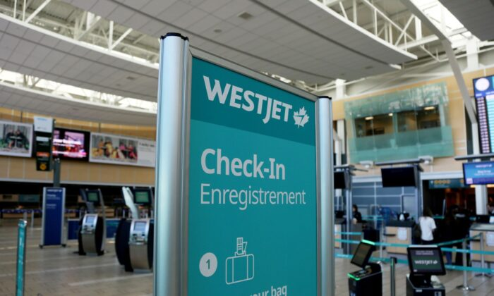 FILE PHOTO: WestJet airline signage is pictured at Vancouver's international airport in Richmond, British Columbia, Canada, February 5, 2019. (Reuters/Ben Nelms/File Photo)