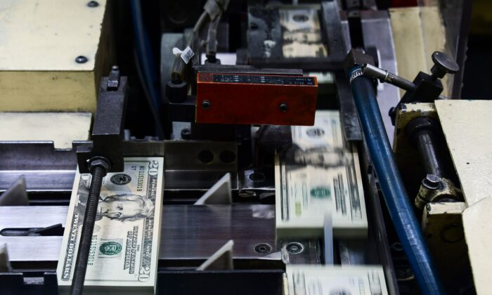 Packs of freshly printed $20 USD notes are processed for bundling at the U.S. Treasury's Bureau of Engraving and Printing in Washington. July 20, 2018.  (Eva Hambach/AFP via Getty Images)