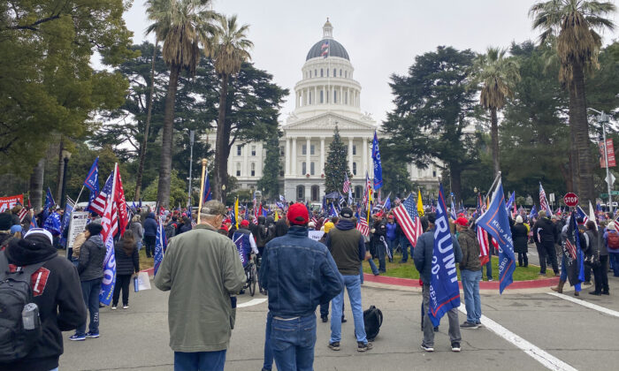 Rally attendees hold signs and flags at the California State Capitol in Sacramento, Calif., on Jan. 6, 2021. (Ilene Eng/The Epoch Times)