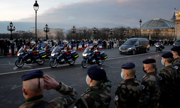 French soldiers stand in an honour guard as the hearse convoy of late French forces soldiers rides on the Alexandre III bridge in central Paris on Thursday, Jan. 7, 2021. (Christophe Ena/AP Photo)
