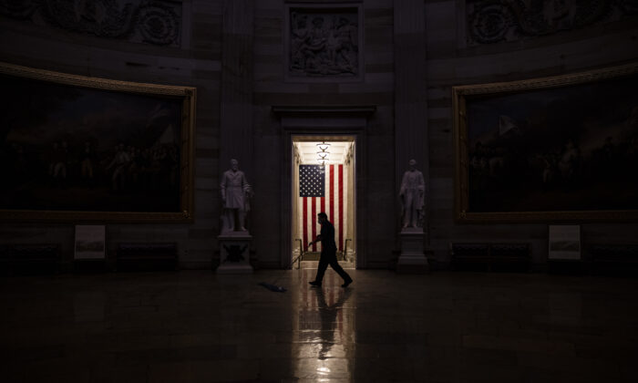 A worker sweeps up the dust and debris that was left behind by protesters in the Rotunda of the U.S. Capitol building on Jan. 7, 2021. (Samuel Corum/Getty Images)