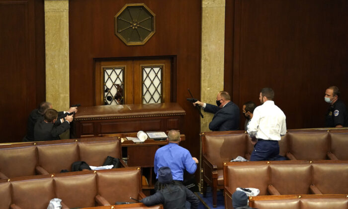 Law enforcement officers point their guns at a door that was vandalized in the House Chamber during a joint session of Congress in Washington, on Jan. 6, 2021. (Drew Angerer/Getty Images)