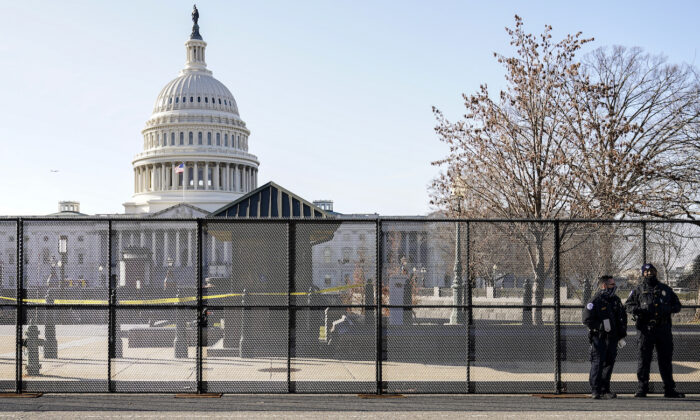 Capitol police officers stand outside of fencing that was installed around the exterior of the Capitol grounds, in Washington on Jan. 7, 2021. (AP Photo/John Minchillo)