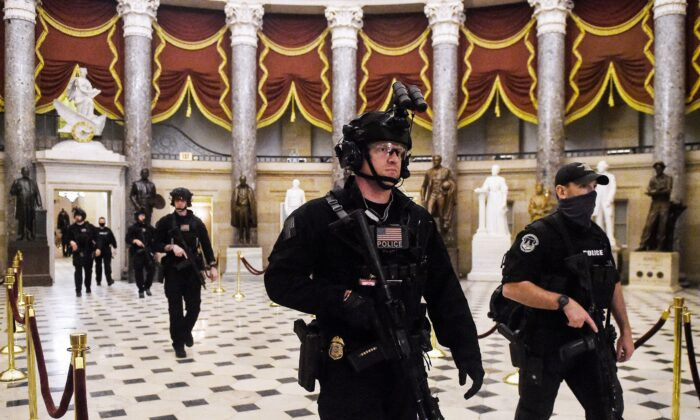 Members of the Swat team patrol and secure the Statuary Hall before Vice President Mike Pence makes his way into the House Chamber, at the US Capitol in Washington on Jan. 7, 2021. (Olivier Douliery/AFP via Getty Images)