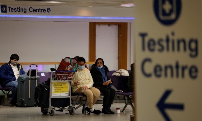 Passengers sit beneath a testing centre sign in the terminal building of Manchester Airport amid the outbreak of the coronavirus disease (COVID-19) in Manchester, Britain, Dec. 3, 2020. (Phil Noble/Reuters File Photo)