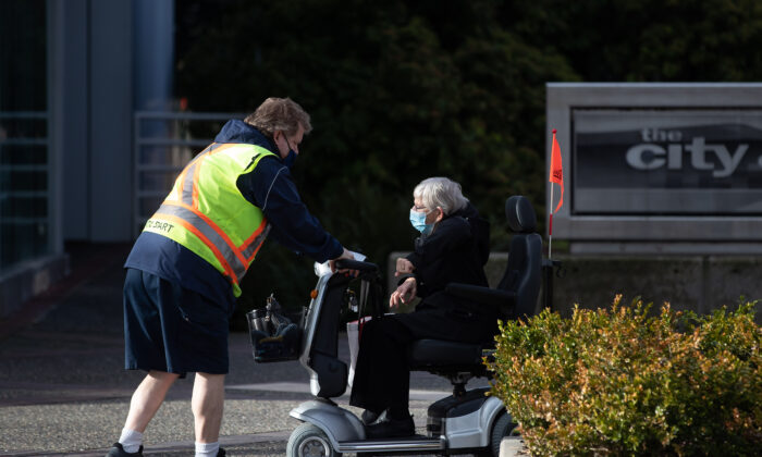 A HandyDART driver helps an elderly person on a mobility scooter after dropping her off in North Vancouver, B.C., Canada, on Jan. 6, 2020. (Darryl Dyck/The Canadian Press)