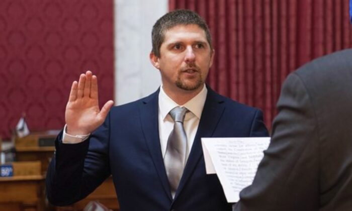 West Virginia House of Delegates member Derrick Evans, left, is given the oath of office in the House chamber at the state Capitol in Charleston, W.V., on Dec. 14, 2020. (Perry Bennett/West Virginia Legislature via AP)