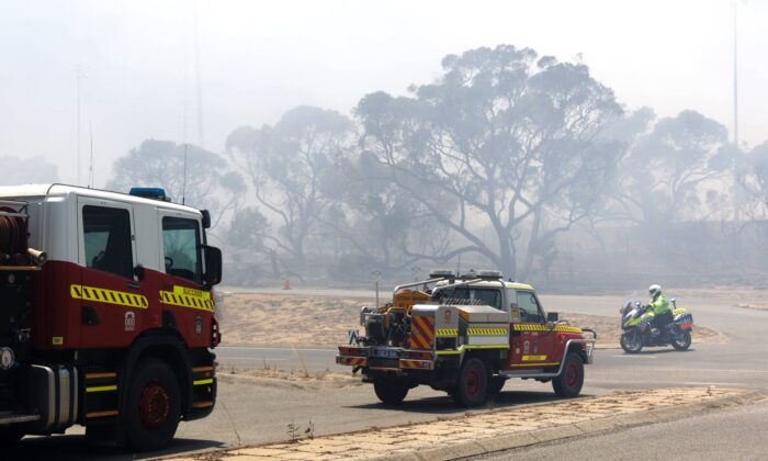 Emergency vehicles patrol the perimeter while battling a bush fire south of Perth on January 4, 2021. (Photo by TREVOR COLLENS/AFP via Getty Images)