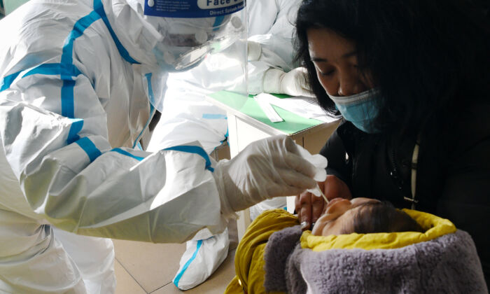 A medical worker takes a swab sample from an infant for COVID-19 test in Shijiazhuang, Hebei Province, China, on Jan. 7, 2021. (STR/CNS/AFP via Getty Images)