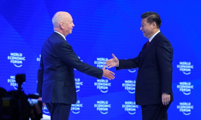 China's leader Xi Jinping (R) shakes hands with founder and executive chairperson of the World Economic Forum, Klaus Schwab (L) prior to delivering a speech to the WEF, in Davos, Switzerland, on Jan. 17, 2017. (Fabrice Coffrini/AFP via Getty Images)