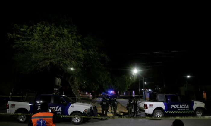 Police stand guard near a crime scene after unidentified gunmen burst into a wake killing several people, according to authorities, in Celaya, Mexico, on Jan. 7, 2021. (Sergio Maldonado/Reuters)