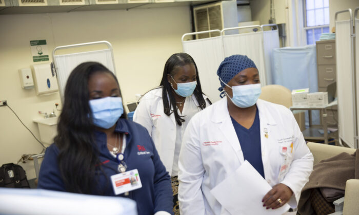 Christine Scott, an ICU nurse (L), with her sisters Althea Scott-Bonaparte and Claudia Scott-Mighty, who are patient care directors, arrived to get their second shot of the Pfizer vaccine at NewYork-Presbyterian Lawrence Hospital in Bronxville, N.Y., on Jan. 8, 2021. (Kevin Hagen/AP Photo).