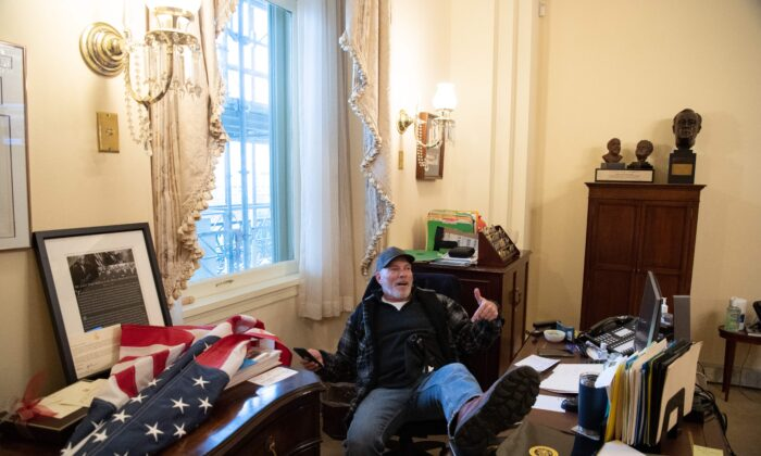 Richard Barnett, a protester, sits inside the office of US Speaker of the House Nancy Pelosi inside the US Capitol in Washington, on Jan. 6, 2021. (SAUL LOEB/AFP via Getty Images)