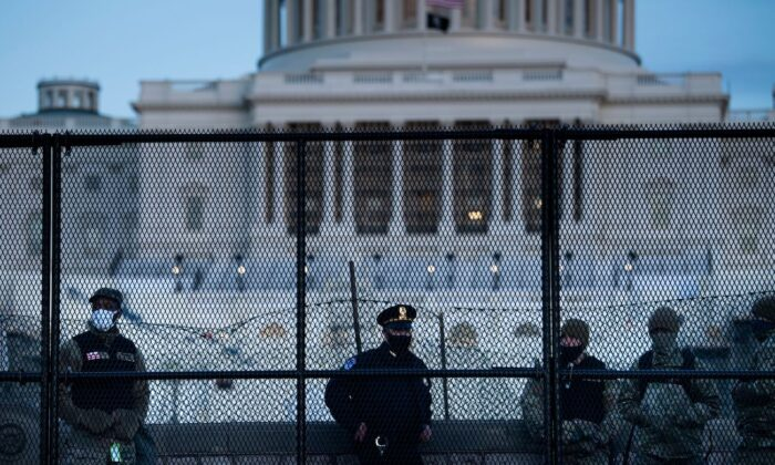A Capitol Police officer stands with members of the National Guard behind a crowd control fence surrounding Capitol Hill a day after a group broke into the U.S. Capitol in Washington, on Jan. 7, 2021. (Brendan Smialowski/AFP via Getty Images)