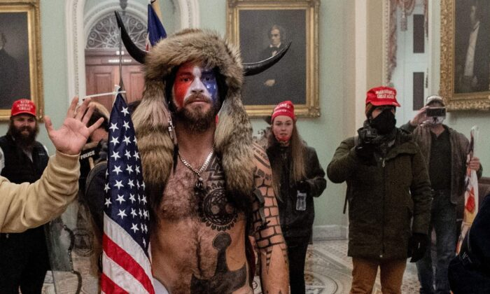Jake Angeli (C) entered the Capitol building during a protest with his painted face and horned hat in Washington, on Jan. 6, 2021. (Saul Loeb/AFP via Getty Images)